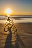 Езда велосипеда на восходе солнца на пляже какао Стоковая Фотография