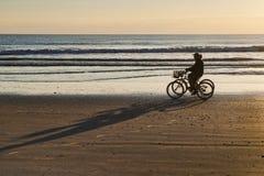 Езда велосипеда на восходе солнца на пляже какао Стоковое фото RF