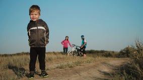 Езда велосипеда семьи Семья вне города Ребенок развевая ручка на предпосылке родителей с велосипедами акции видеоматериалы