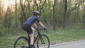 Езда велосипеда спасения в парке с солнцем светя через деревья Кинематографическая задействуя концепция видеоматериал
