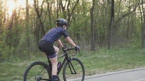 Езда велосипеда спасения в парке с солнцем светя через деревья Кинематографическая задействуя концепция ( видеоматериал