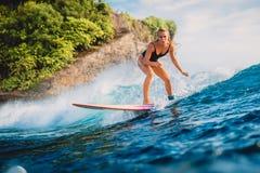 Езда женщины серфера на surfboard на океанской волне Женщина в океане во время серфинга Стоковое Изображение