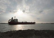 Езда корабля нефти и газ через реку с небом захода солнца как предпосылка Стоковое Изображение RF