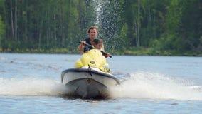 Езда мамы и дочери вдоль реки на личном watercraft сток-видео