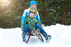 Езда матери и сына на санях Детская игра в потехе зимы снежного леса на открытом воздухе на каникулы рождества семьи стоковое изображение