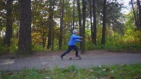 Езда ребенка мальчика скейтбордиста на коньке на открытом воздухе в парке осени