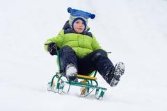 Езда скелетона мальчика на горе снега в зиме стоковое изображение