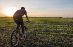 Езда человека велосипед в заходе солнца Ехать велосипед на заходе солнца уклад жизни принципиальной схемы здоровый Мужской велоси Стоковое Изображение