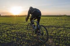 Езда человека велосипед в заходе солнца Ехать велосипед на заходе солнца уклад жизни принципиальной схемы здоровый Мужской велоси Стоковые Изображения
