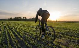 Езда человека велосипед в заходе солнца Ехать велосипед на заходе солнца уклад жизни принципиальной схемы здоровый Мужской велоси Стоковые Фото