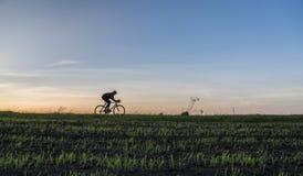 Езда человека велосипед в заходе солнца Ехать велосипед на заходе солнца уклад жизни принципиальной схемы здоровый Мужской велоси Стоковая Фотография