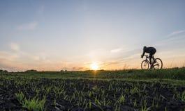 Езда человека велосипед в заходе солнца Ехать велосипед на заходе солнца уклад жизни принципиальной схемы здоровый Мужской велоси Стоковая Фотография RF