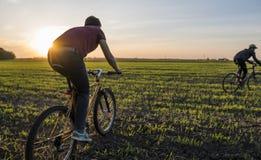 Езда 2 человек велосипед в заходе солнца Ехать велосипед на заходе солнца уклад жизни принципиальной схемы здоровый Мужской велос Стоковые Фотографии RF