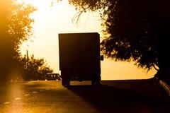 Езды автомобиля на дороге на заходе солнца Стоковые Фотографии RF