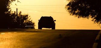 Езды автомобиля на дороге на заходе солнца Стоковые Фото