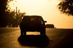 Езды автомобиля на дороге на заходе солнца Стоковое фото RF