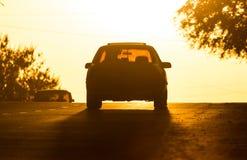 Езды автомобиля на дороге на заходе солнца Стоковые Изображения