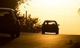 Езды автомобиля на дороге на заходе солнца Стоковая Фотография RF