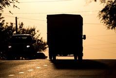 Езды автомобиля на дороге на заходе солнца Стоковые Изображения RF