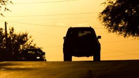 Езды автомобиля на дороге на заходе солнца Стоковое Фото