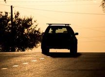 Езды автомобиля на дороге на заходе солнца Стоковая Фотография