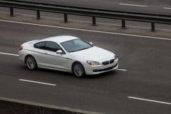 Езды белизны coupe BMW на дороге Против предпосылки запачканных деревьев стоковые фото