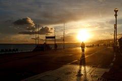 Езды велосипедиста вдоль прогулки против неба захода солнца стоковая фотография
