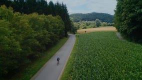 Езды велосипедистов на велосипеде на дороге поля леса акции видеоматериалы