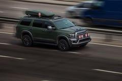 Езды зеленого цвета Тойота на дороге Против предпосылки запачканных деревьев стоковое изображение