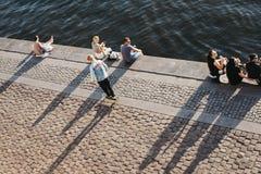 Езды конькобежца наряду с людьми сидя на обваловке реки Влтавы в Праге, чехии стоковое изображение