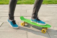 Езды маленькой девочки скейтборд, в районе около дома, весенний сезон, серая предпосылка стены стоковое изображение