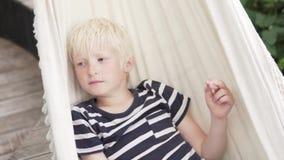 Езды мальчика белокурые гамак на ферме летом акции видеоматериалы