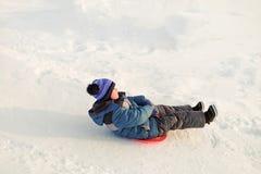 Езды мальчика на лед-шлюпке от скольжения снега стоковая фотография