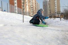 Езды ребенка sledding вниз Стоковые Фото