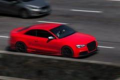 Езды спорта coupe Audi красные на дороге Против предпосылки запачканных деревьев стоковая фотография