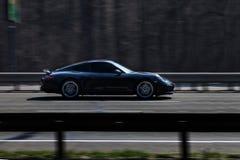 Езды черноты Порше 911 Carrera на дороге Против предпосылки запачканных деревьев стоковые фотографии rf
