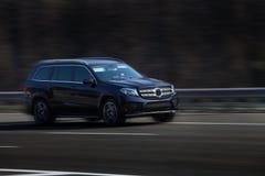 Езды черноты Benz GL Мерседес на дороге Против предпосылки запачканных деревьев стоковая фотография