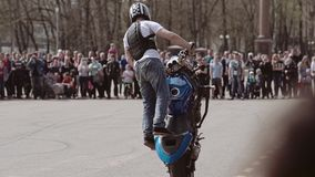 Езды эффектного выступления мотоциклиста на заднем колесе на мотоцикле представляя для аудитории на мотор-шоу Хороший каскадер видеоматериал