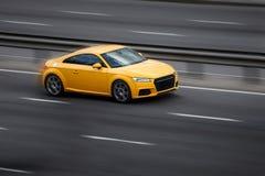 Езды Audi желтые на дороге Против предпосылки запачканных деревьев стоковая фотография
