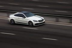 Езды coupe Benz Мерседес белые на дороге Против предпосылки запачканных деревьев стоковое изображение rf
