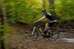 Езды Mountainbiker через поток леса Стоковое Изображение