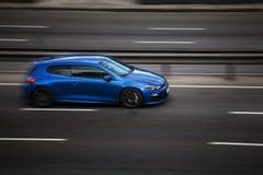 Езды scirocco VW голубые на дороге Против предпосылки запачканных деревьев стоковые изображения