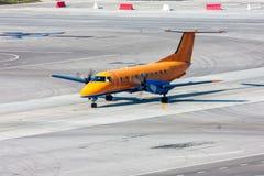 Ездя на такси самолет турбовинтового самолета на рисберме авиапорта Стоковые Изображения RF