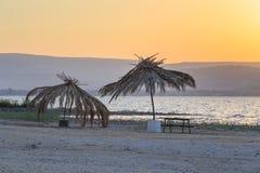 дезертированный пляж Озеро Kineret Старый зонтик соломы ладони Стоковая Фотография RF