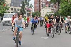 Езда велосипеда молодости через улицы города Стоковое Изображение RF