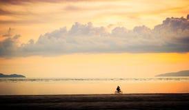 Езда велосипеда на заходе солнца Стоковые Фото