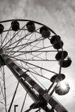 Езда занятности ярмарочной площади колеса Ferris на заходе солнца Стоковая Фотография