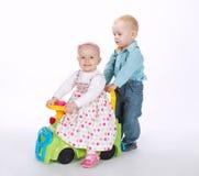 Езда мальчика и девушки на автомобиле игрушки Стоковая Фотография