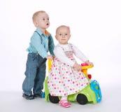 Езда мальчика и девушки на автомобиле игрушки Стоковые Изображения RF