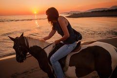 Езда лошади на заходе солнца Стоковое фото RF